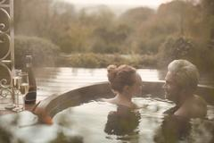 Couple talking soaking in hot tub with champagne on autumn patio Stock Photos