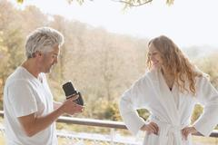 Man with old-fashioned camera photographing woman in bathrobe on autumn balcony Stock Photos