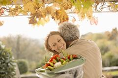 Husband surprising wife with flower bouquet on autumn patio Stock Photos