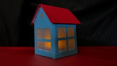 Cardboard house with flickering flame inside Stock Footage