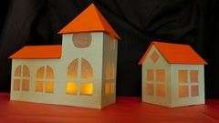 Cardboard church and house with flickering flame inside Stock Footage