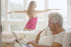 Woman practicing yoga warrior 2 pose in bedroom with husband using laptop in bed Stock Photos