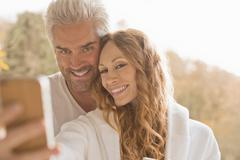 Affectionate couple smiling taking selfie with camera phone outdoors Stock Photos