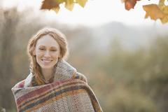 Portrait smiling woman wrapped in blanket in autumn park Stock Photos