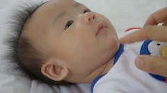 Slow motion of young Asian mother playing with her newborn child, Family at home Stock Footage