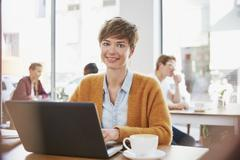 Portrait smiling businesswoman drinking coffee working at laptop in cafe Stock Photos