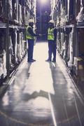 Workers handshaking in aisle of distribution warehouse Stock Photos