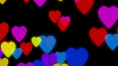 Colorful hearts slowly falling down on a dark background with particles Stock Footage