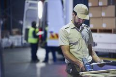 Truck driver worker scanning pallet at distribution warehouse loading dock Stock Photos