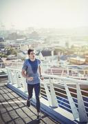Sweaty male runner running on sunny urban footbridge at sunrise Stock Photos