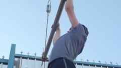 A young man with a beard doing pull-ups in urban environment, slow motion. Stock Footage