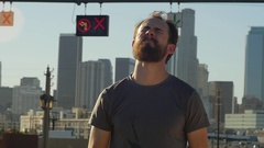 A young man with a beard pouring water over his head after an intense workout, s Stock Footage