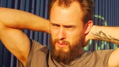 A young man with a beard stretching and working out in urban environment, slow m Stock Footage