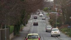 Cars driving down urban English street  with houses and row of trees in Autum Stock Footage
