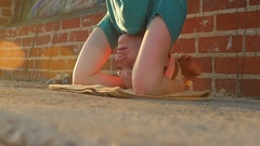 A young woman doing a headstand on the streets on an urban environment, slow mot Stock Footage