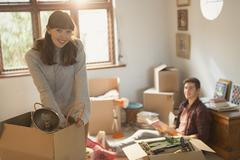 Portrait smiling young couple unpacking moving boxes in apartment Kuvituskuvat