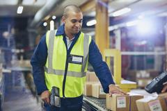 Worker with scanner scanning and processing boxes on conveyor belt in Stock Photos