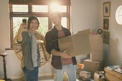Young men roommates taking selfie moving boxes in apartment Kuvituskuvat