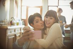 Playful young friends taking selfie with camera phone making a face Stock Photos
