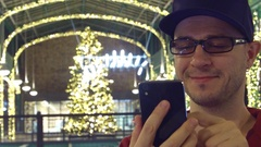 Happy man in black rim glasses scrolls app in his mobile phone in a Christmas Stock Footage
