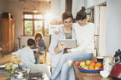 Smiling young couple using digital tablet in kitchen Stock Photos
