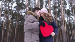 Young happy couple holding red heart together guy and girl holding the heart in Stock Footage