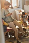 Young woman texting with cell phone in new apartment Stock Photos