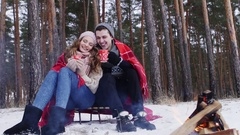 Couple holding bengal light in the winter forest slider shot Stock Footage