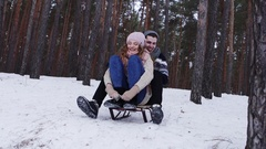 Guy and his girlfriend riding down a steep hill on a toboggan Stock Footage