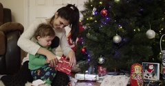 Beautiful young mother and son smiling and unwrapping gift near Christmas tree Stock Footage