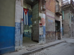 Entrance to the ragged house with cuban flag on street of Havana Stock Footage