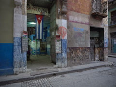 Panoramic view to entrancee of the ragged house with cuban flag on street in Stock Footage