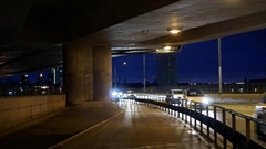 Traffic under bridge at night. Cars and subway train passing by Stock Footage