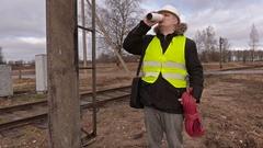 Railway electrician drink coffee near railway Stock Footage