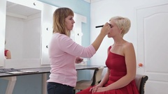 Makeup artist applying liquid tonal foundation on the face of the woman Stock Footage