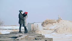 Young guy and girl in winter wear, embrace and enjoy the scenery of winter Stock Footage