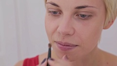Close up shot. Make-up artist applying makeup on the face of the sensual model Stock Footage