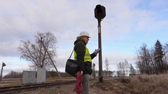 Railway electrician with cable talking on phone near signal beacon on railway Stock Footage