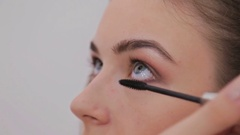Close up shot.Professional make-up artist applying mascara on eyelashes of model Stock Footage