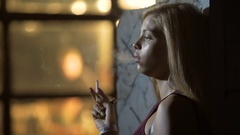 Sexy blonde woman standing near night club and smoking a cigarette, relaxation Stock Footage