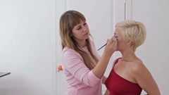 Professional make-up artist applying eyeliner around the entire eye of model Stock Footage
