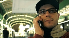 Happy programmer in black rim glasses talking on his mobile phone in a cafe. 4K Stock Footage