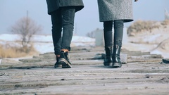 Young beautiful couple in a coat, walks on the bridge of planks, around the snow Stock Footage