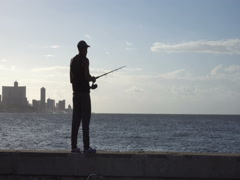 Young man is fishing on the pier at sunset Stock Footage