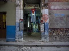 View to entrance of the ragged house with cuban flag on street in Havana Stock Footage