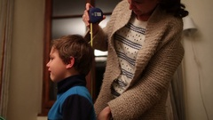 Mother measures child's height while kid cries. Child crying Stock Footage