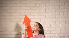 Teen girl in pink shirt show something by red arrow Stock Footage