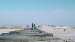 Young guy and girl in winter wear, walking on the bridge of planks, a beautiful Stock Footage
