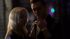 Man flirting with woman at party, people smoking in night club, bad habits Stock Footage