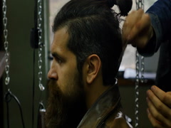 Men's hairstyling and hair cutting in a barbershop or hair salon. Stock Footage